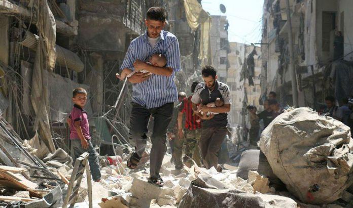 Homens carregam bebês em meio aos escombros, após ataque aéreo na Síria