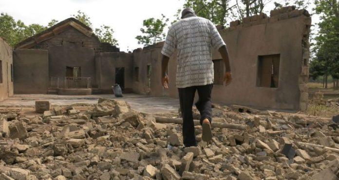 Pastor caminha em frente a sua igreja destruída pelos fulanis, na Nigéria