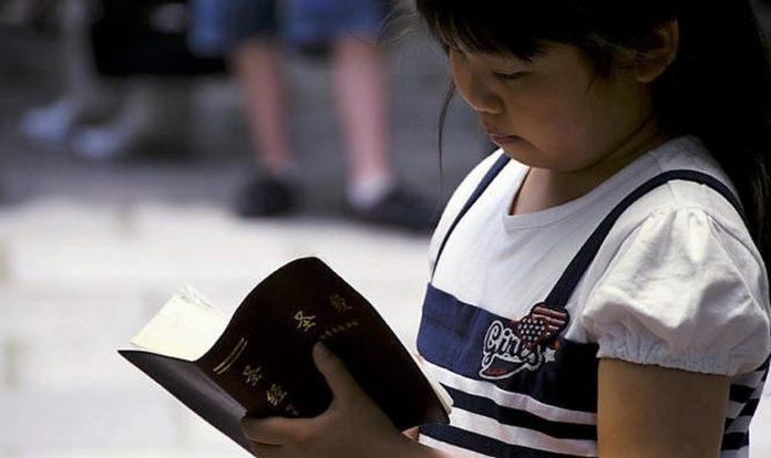 Criança chinesa lendo a Bíblia