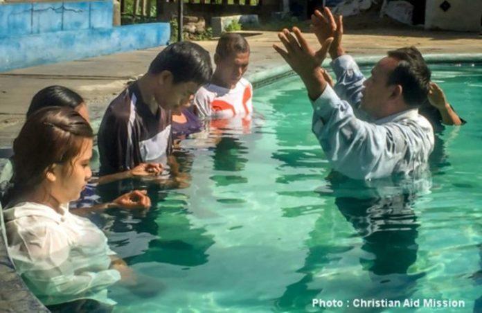Um pastor batiza novos cristãos convertidos na Indonésia.