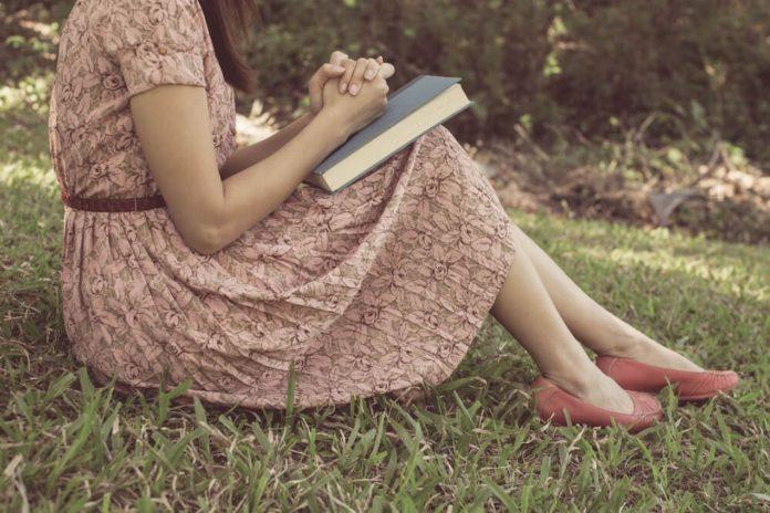 Mulher com a Bíblia orando