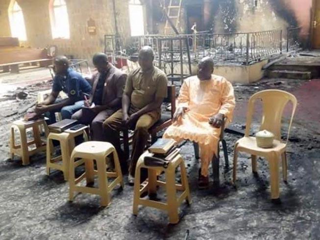 Os anciãos da igreja nigeriana realizam o culto de domingo em meio às cinzas de sua igreja (Foto: Reprodução / Barnabas)