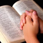 Mãos postas sobre a Bíblia durante oração