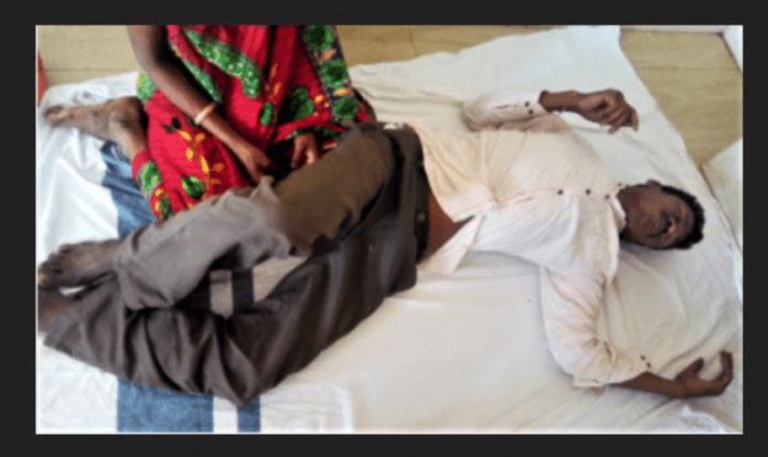 Kama Sodi diante de sua esposa, depois de aldeões animistas o espancarem no estado de Odisha, na Índia.