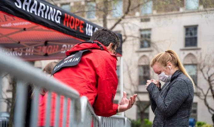 Capelão Charlie Clark ora pela moradora de Nova York, Jennifer Armitage, em frente à tenda de oração. (Foto: Billy Graham Evangelistic Association)