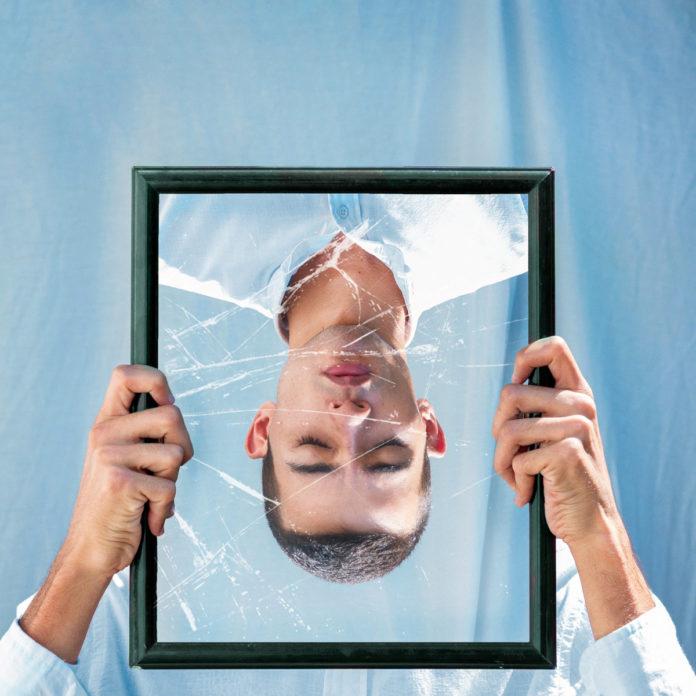 Imagem invertida de um homem em um espelho quebrado (Ilustração)