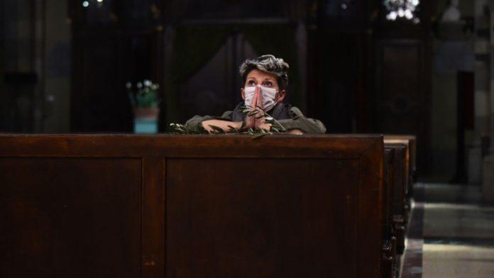 Fiel católica rezando em uma igreja na Itália, durante pandemia do coronavírus.