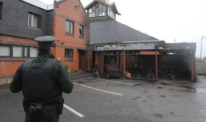 Policial observa igreja incendiada na Irlanda do Norte. (Foto: Reprodução / Bíblia Todo)