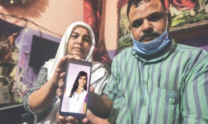 Os pais seguram uma foto da cristã Arzoo Raja forçada a casar com um muçulmano, no Paquistão