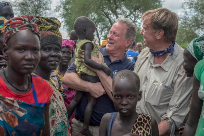 O Diretor Executivo do Programa Mundial de Alimentos David M. Beasley (segurando uma criança) e o Embaixador dos EUA Kip Tom visitam o Sudão do Sul em 23 de julho de 2019. | PMA / Giulio d'Adamo