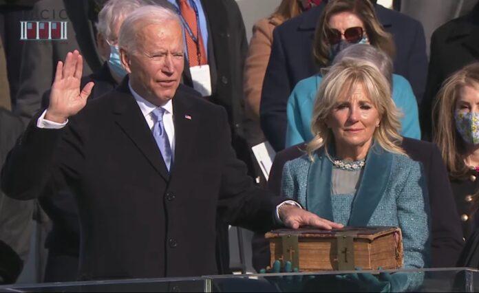 Joe Biden durante juramento na sua posse com a mão em uma Bíblia.
