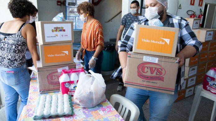 Equipe da Visão Mundial durante distribuição de alimentos.