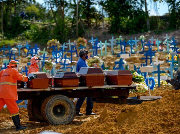 Coveiros levam caixões com pessoas mortas por covid-19 no Cemitério Público Nossa Senhora Aparecida, em Manaus.