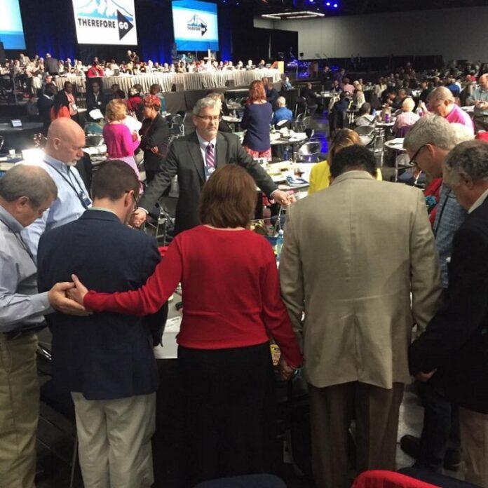Delegados oram antes de uma sessão plenária na Conferência Geral da Igreja Metodista Unida 2016 em Portland, Oregon. (Foto: Conferência Geral do Facebook / Metodista Unida)