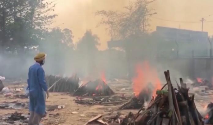 Um profissional de saúde supervisiona cremações ao ar livre em Delhi.