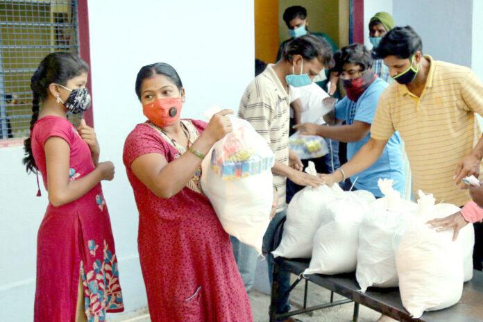 Pessoas na Índia recebem alimentos