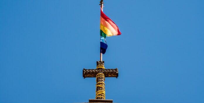 Bandeira LGBT sobre uma cruz no topo de uma igreja