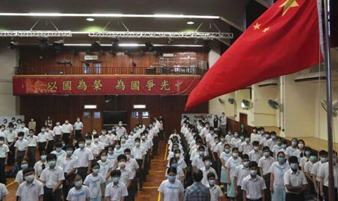 Alunos participam de uma cerimônia de hasteamento da bandeira, no Dia da Educação para a Segurança Nacional, numa escola em Hong Kong,