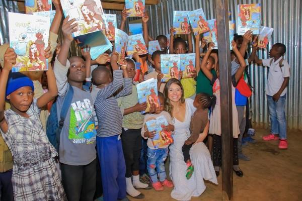 Júlia Malucelli com crianças segurando o livro